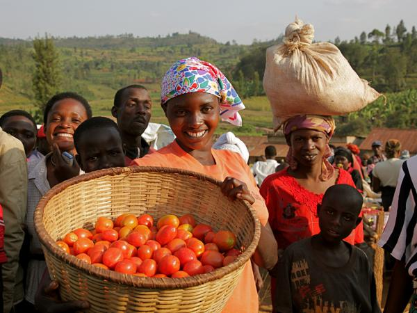 Victoria sells ripe, red tomatoes at bustling Kirambi market, south Rwanda. More than 60 percent of chronically hungry people are women. Trócaire helps young people like Victoria begin small businesses so their future families won't be hungry.
