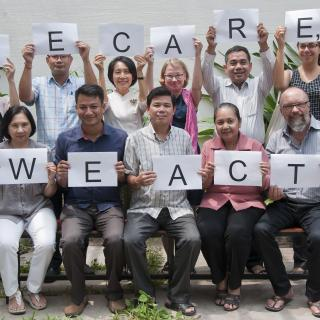 Group of project participants at the launch of the project in Cambodia, holding signs saying We care, we act