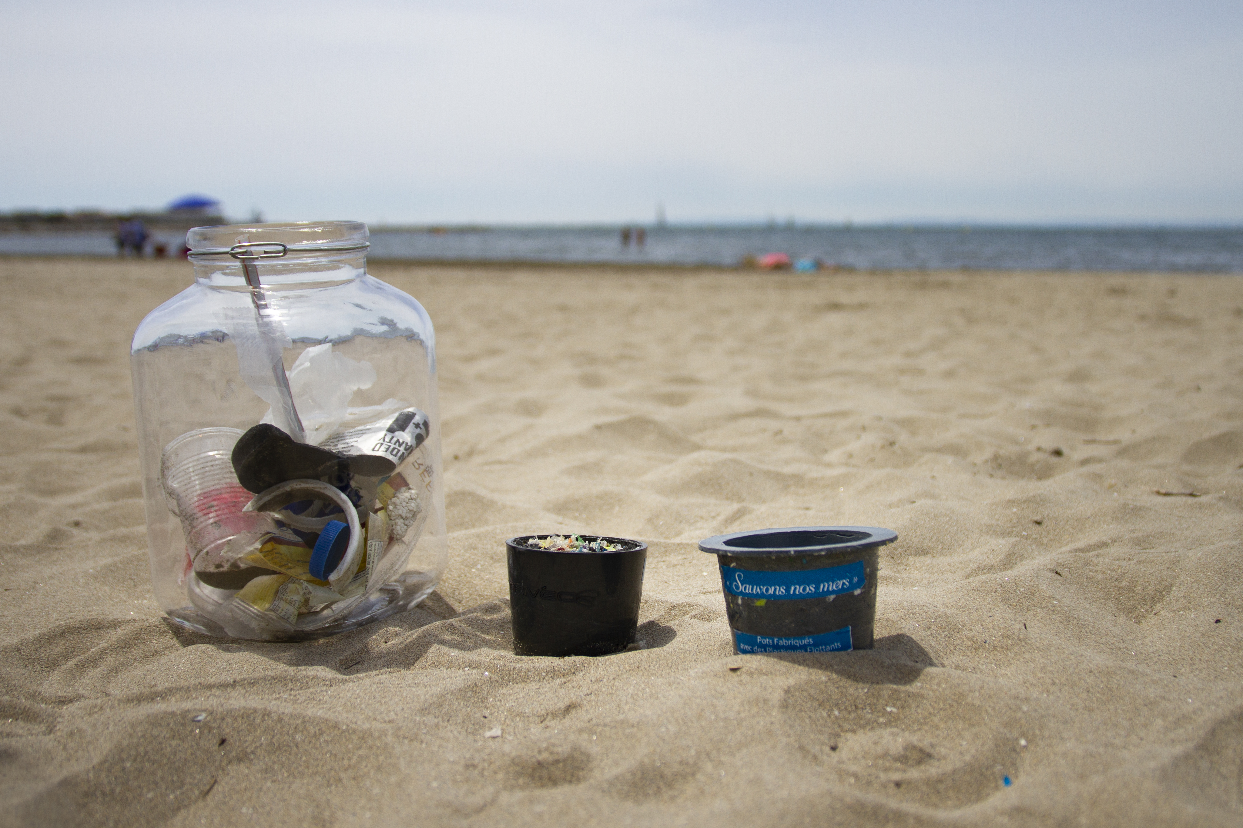 glass jar on beach with plastic waste collected by ReSeaclons